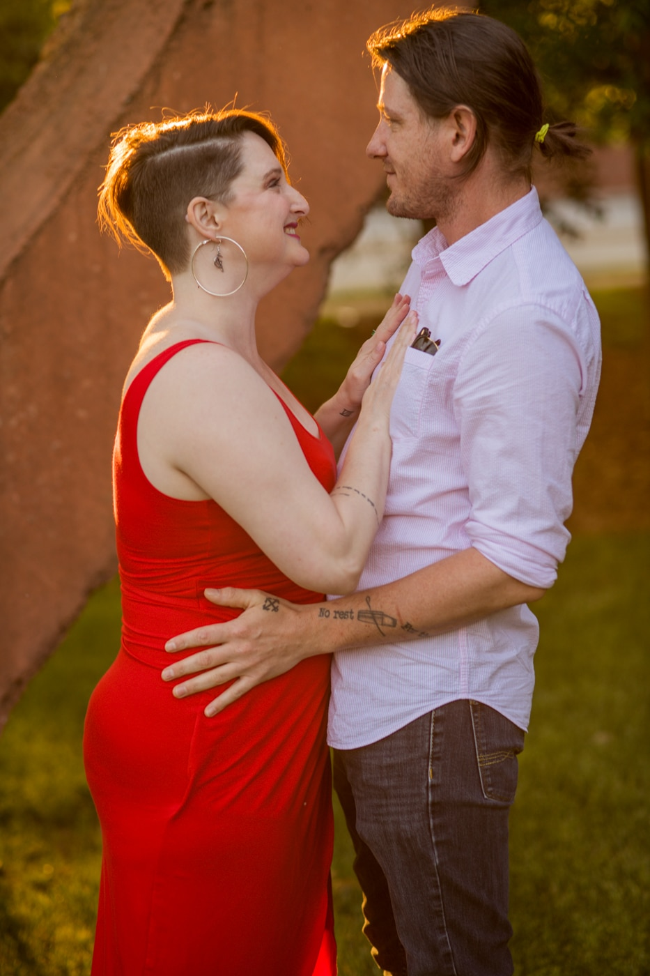 engaged couple hugs at sunset by sculpture in Charlotte NC