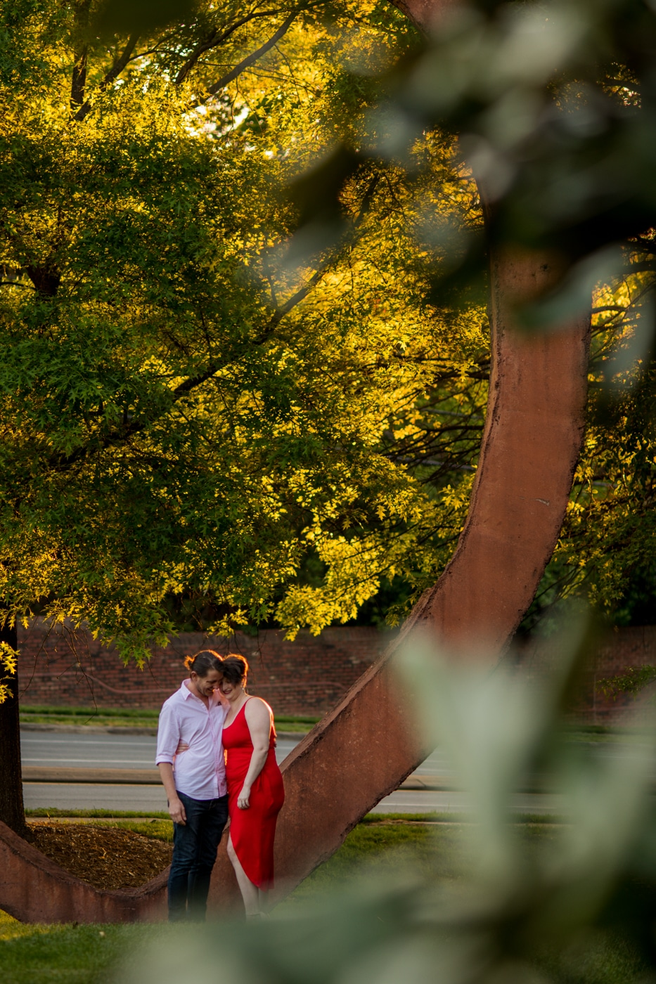couple sits on copper sculpture in Charlotte NC
