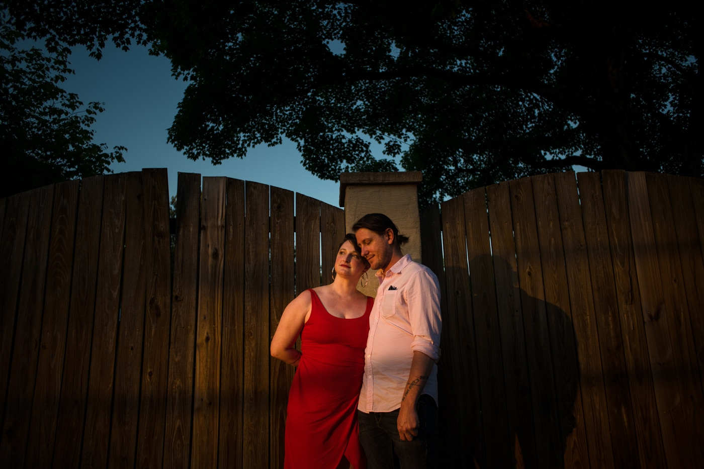 engaged couple poses by fence in backyard