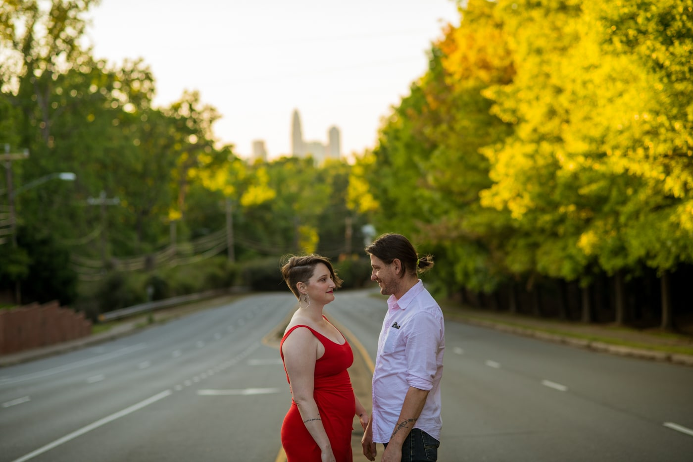 bride and groom pose in front of Charlotte skyline