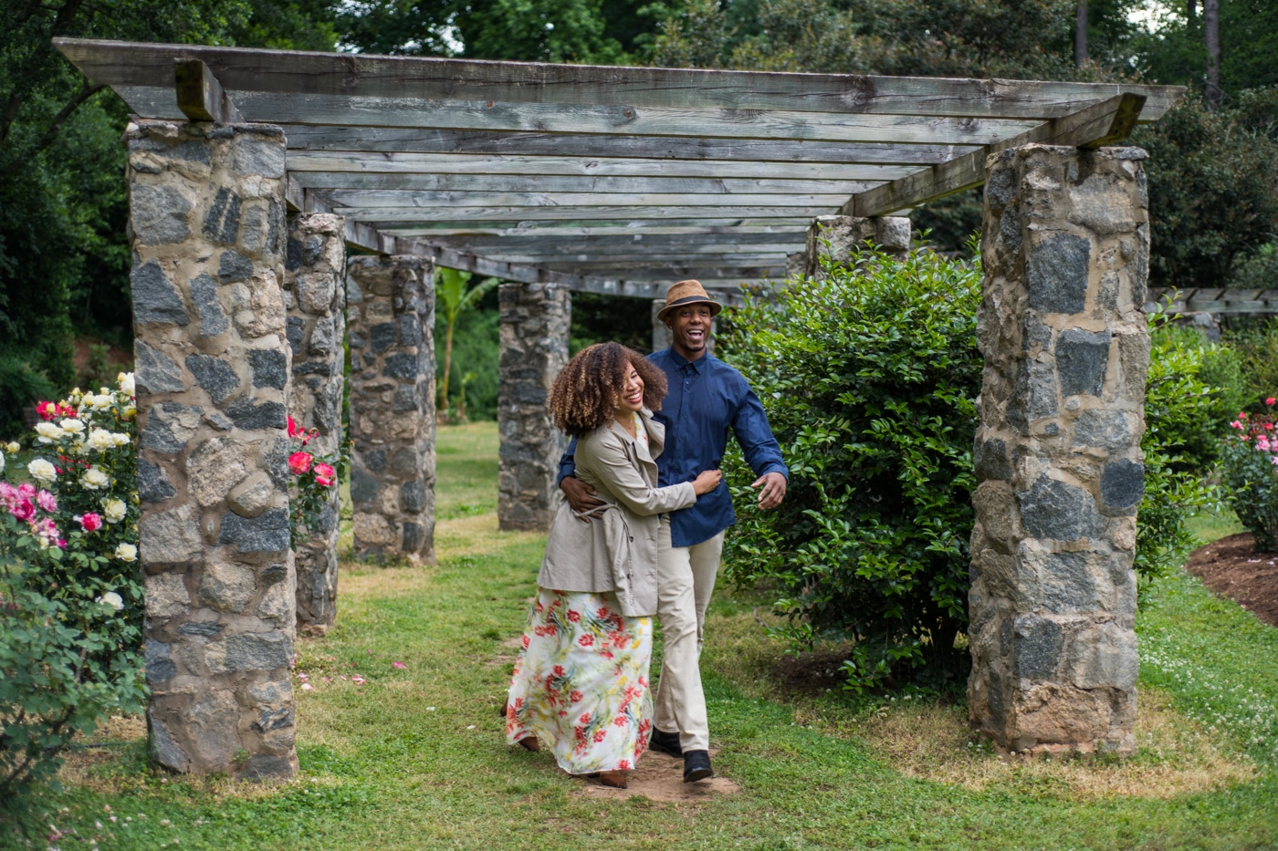 couple walks under stone arbor at Raleigh Rose Garden