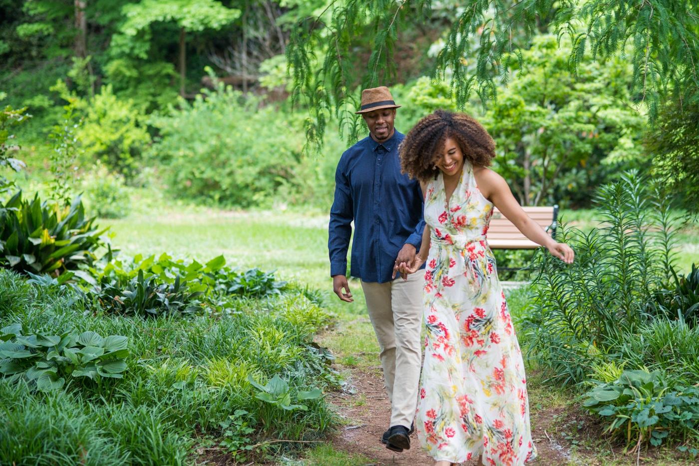 couple laughs walking through path in Raleigh Rose Garden