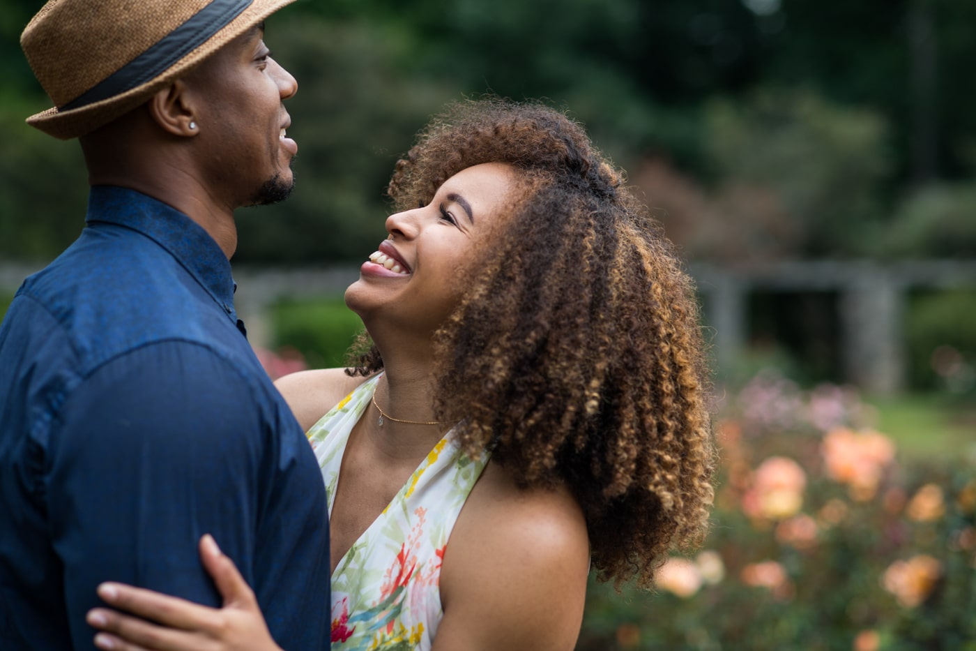woman laughs at partner in field of roses