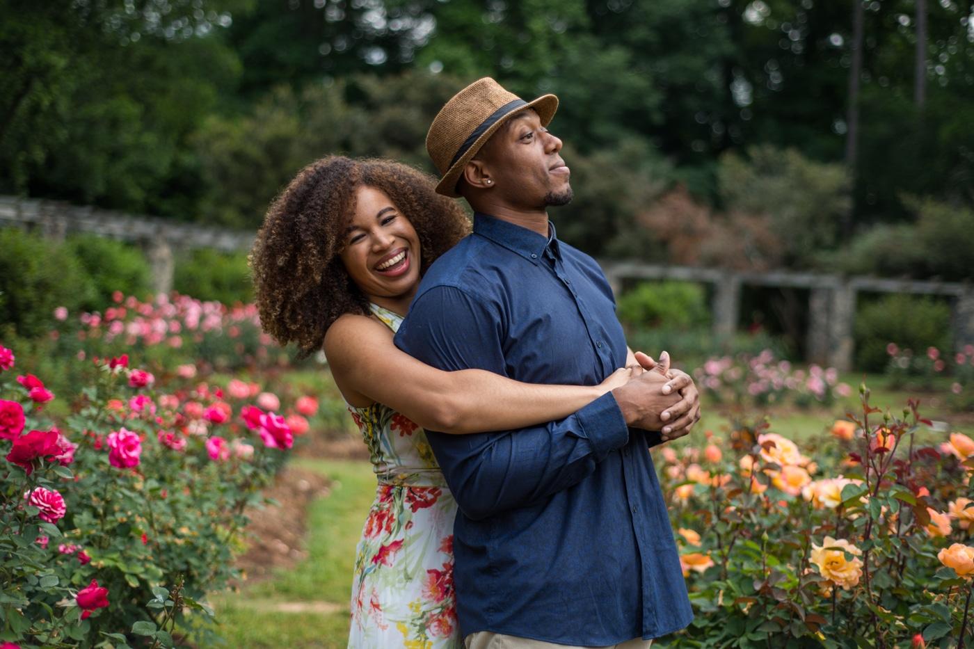 woman hugs partner during Raleigh Rose Garden portrait session