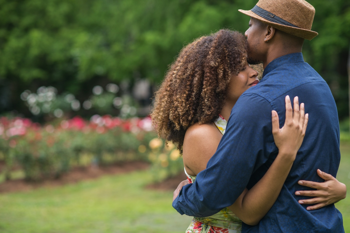 man kisses woman's forehead during Raleigh Rose Garden portrait session