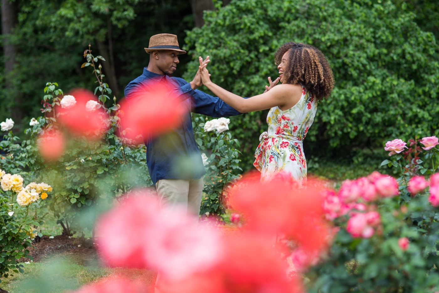playful portraits of couple in rose garden