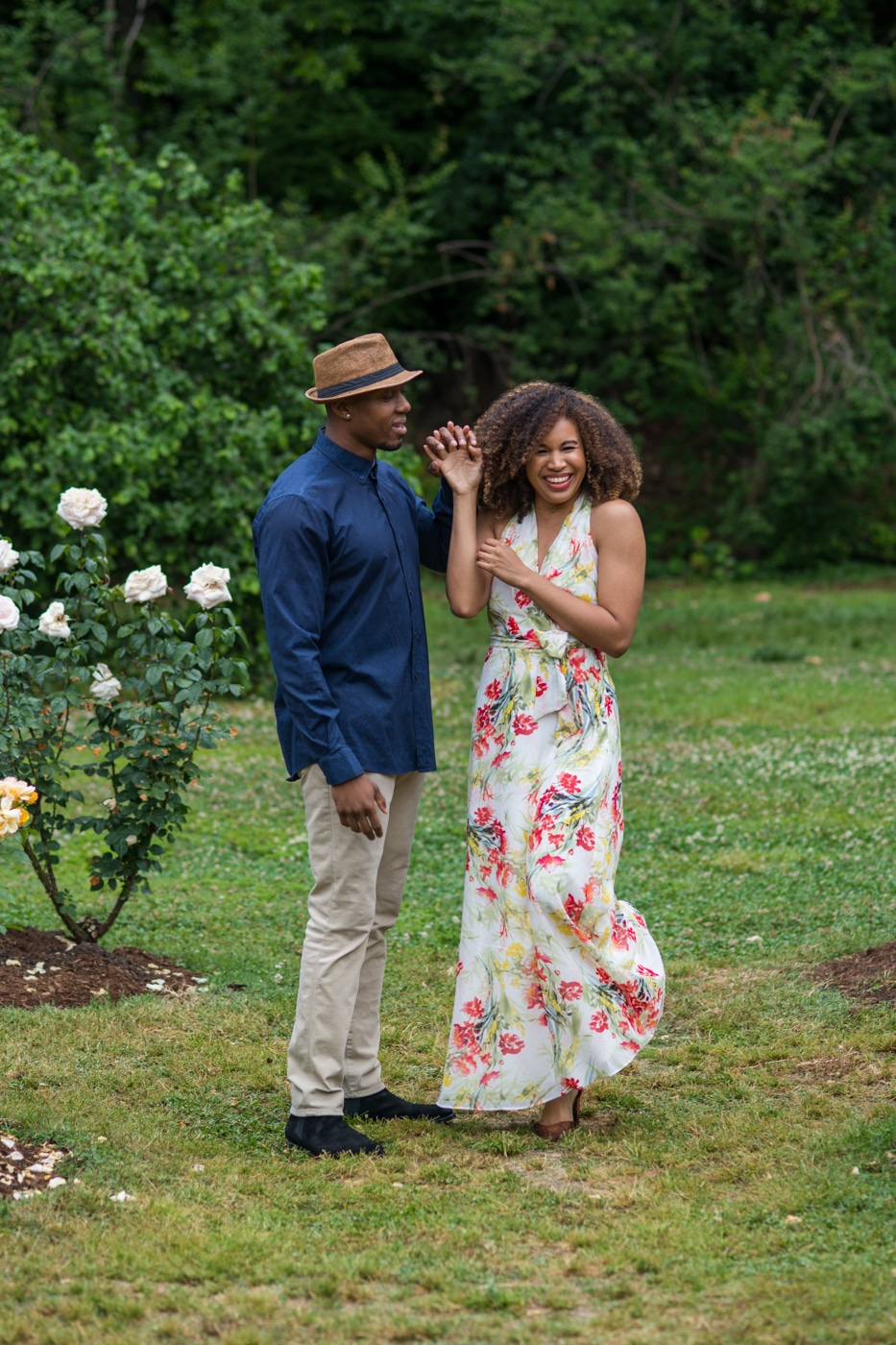 couple dances among white roses during Raleigh Rose Garden portrait session