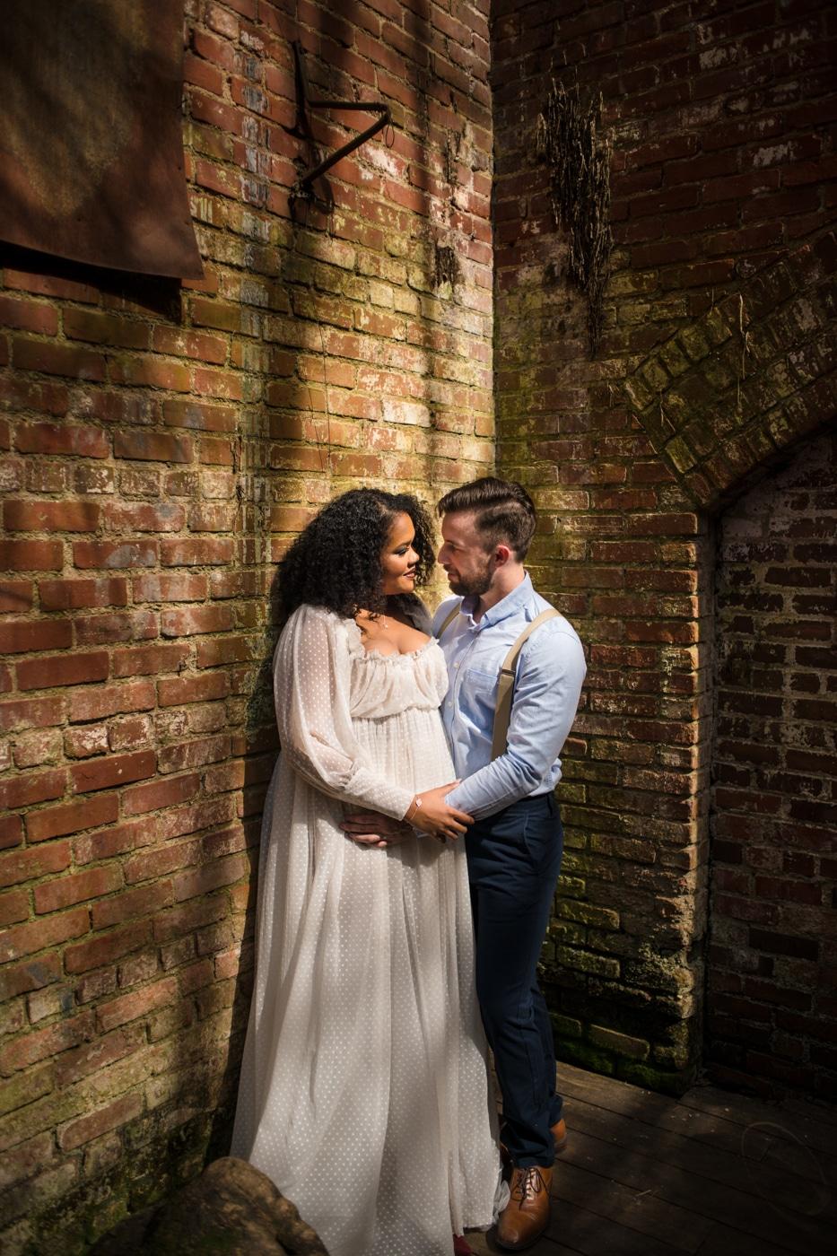 couple poses in corner of brick walls in Athens GA