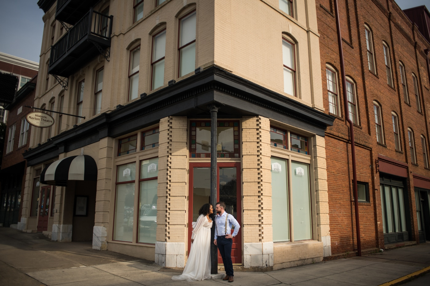 newlyweds pose by metal pole outside building in Athens GA