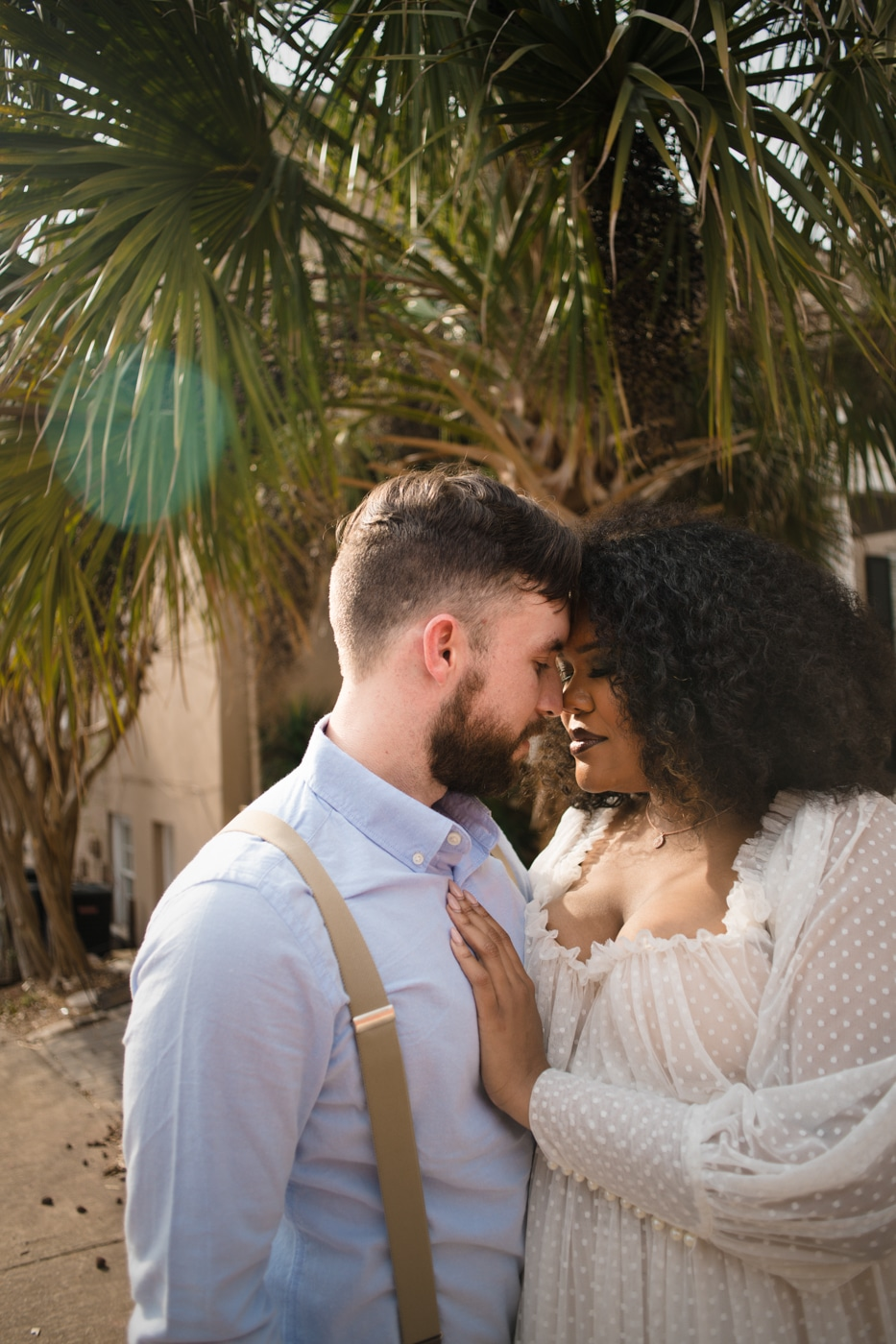 newlyweds stand nose to nose under palm tree in Athens GA