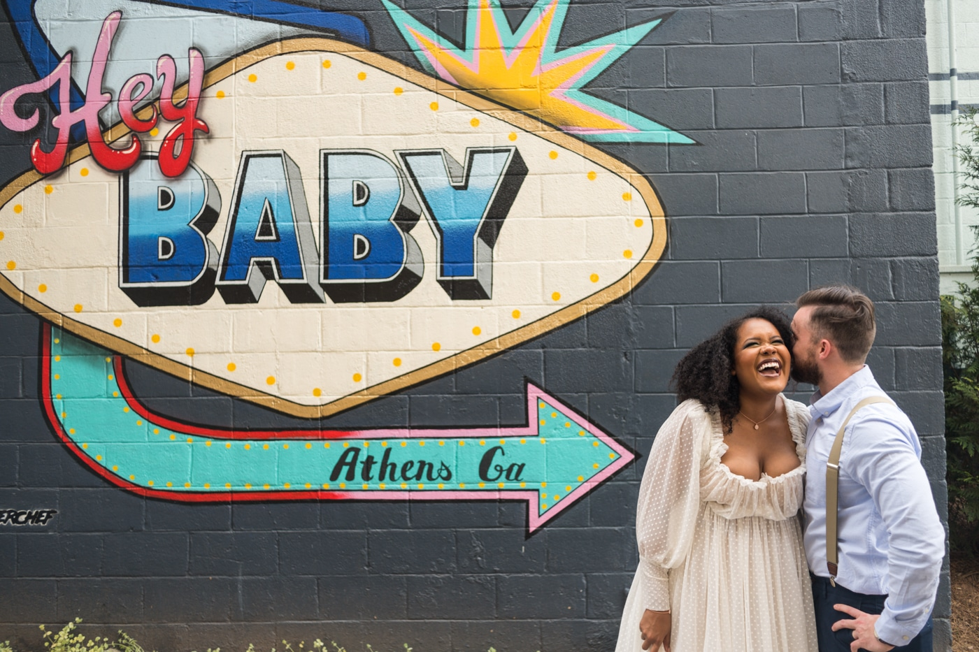 "groom makes bride laugh by ""Hey Baby"" mural"