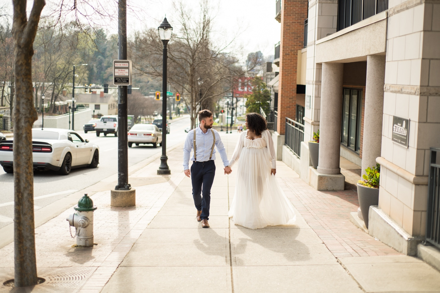 newlyweds hold hands walking down street in Athens GA