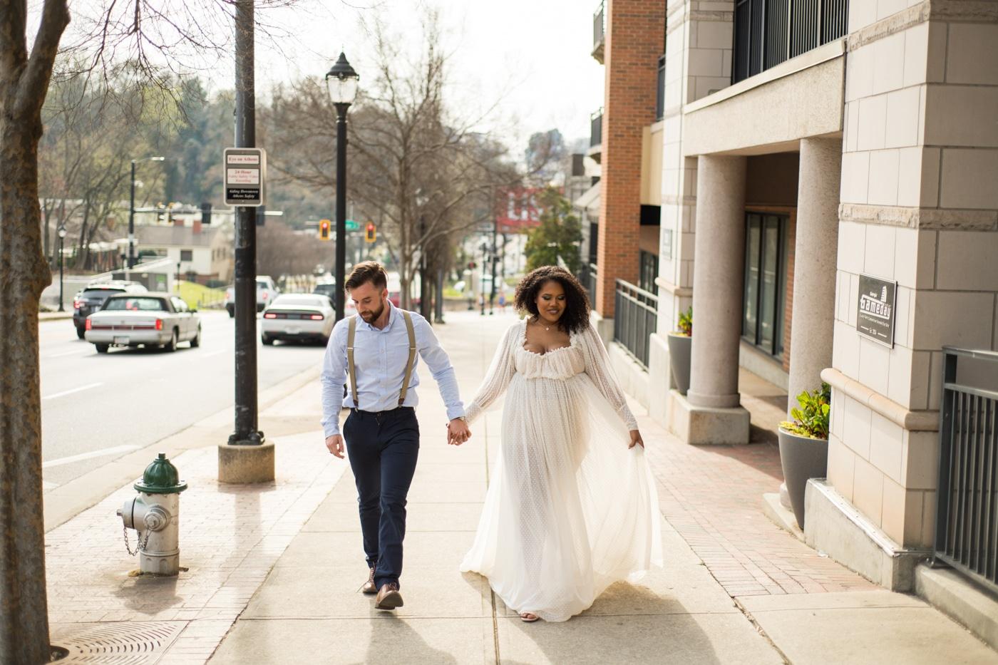 bride and groom laugh walking down road in Athens GA