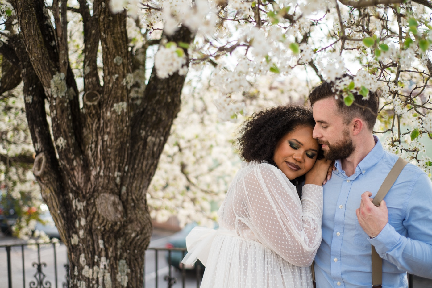 bride and groom pose under white blossoms in Athens GA