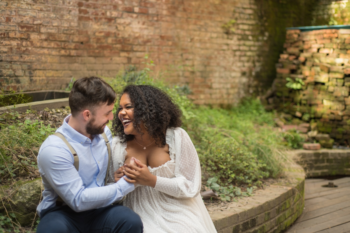 married couple sits on brick wall at Tree Room