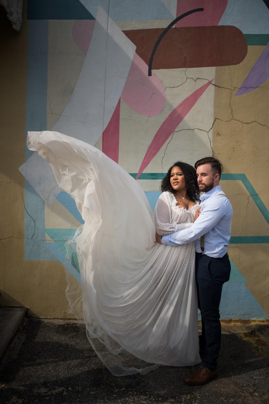 groom hugs bride with dress floating in air by mural in Athens, GA