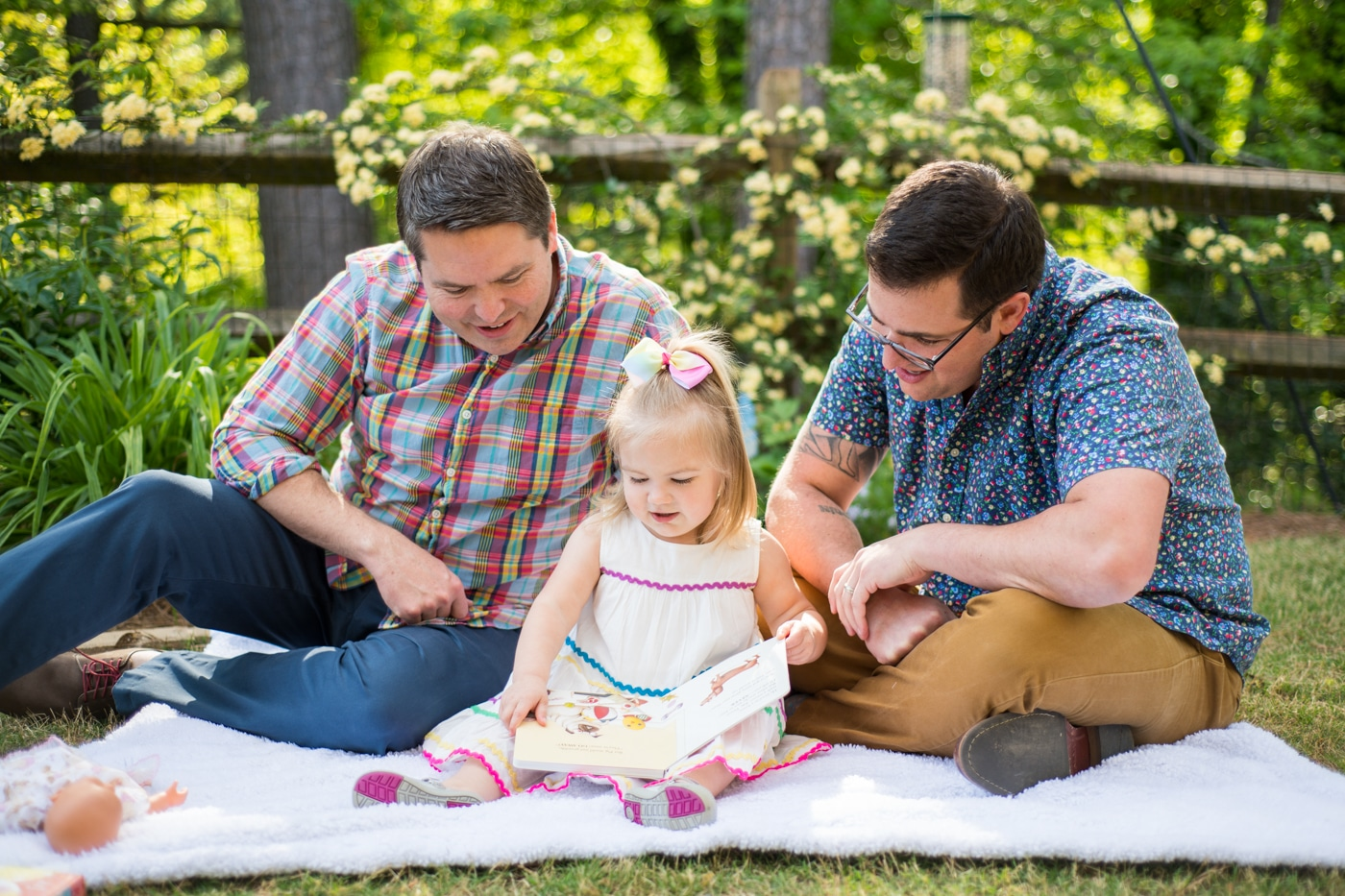 A Family sitting on a blanket with their toddler reading a kids book in Atlanta Raven Shutley Studios