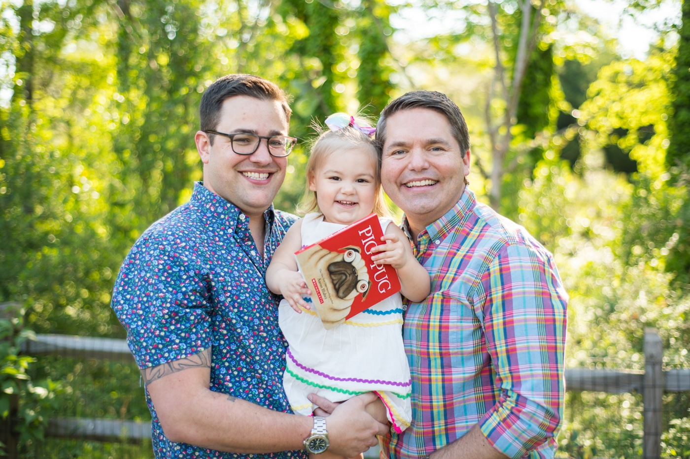 Dads smiling with their toddler holding a book during family photos in Atlanta by Raven Shutley