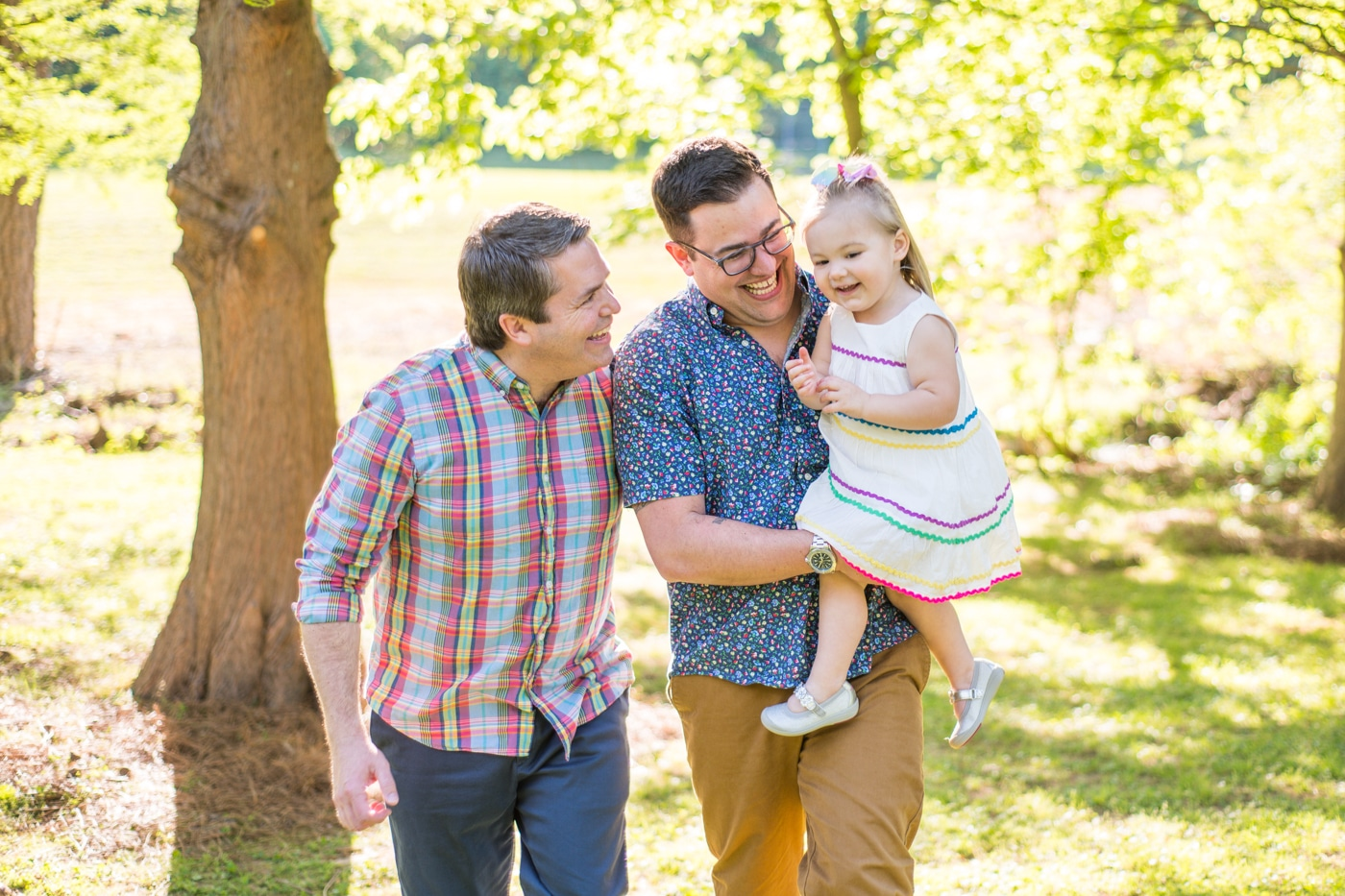 Two dads smiling and holding their toddler outside on a sunny day in Atlanta Raven Shutley Studios