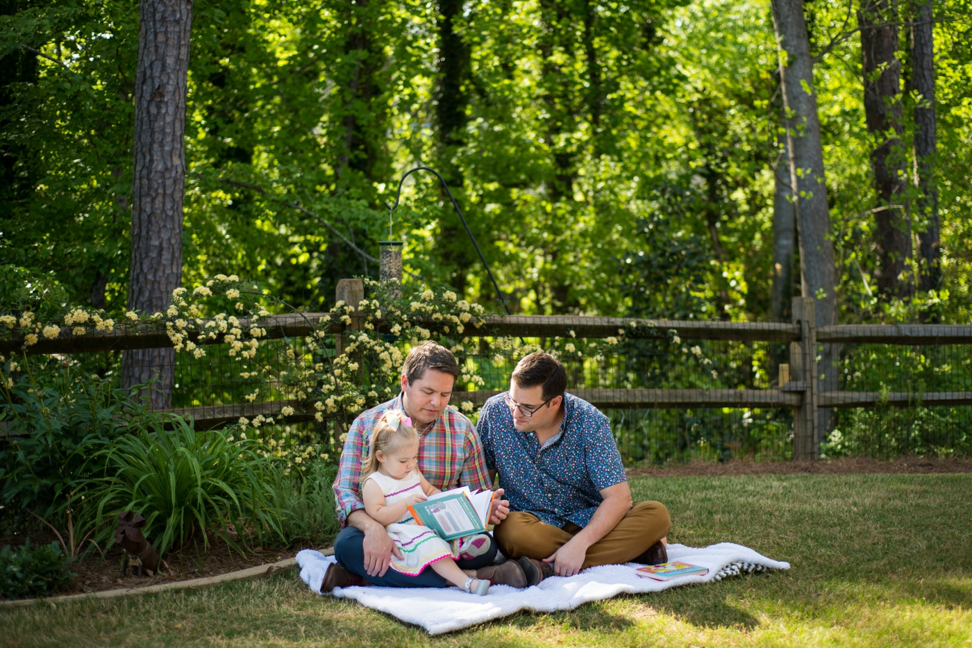 Young parents sitting with their toddler on a blanket at Atlanta home Raven Shutley family portraits