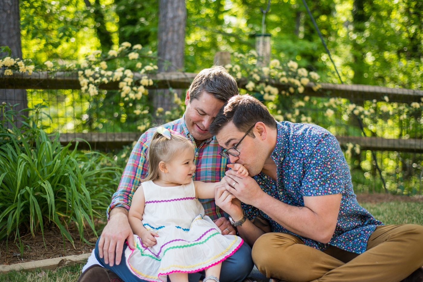 Dad kisses his toddler's hand during family photos in their Atlanta backyard Raven Shutley Studios