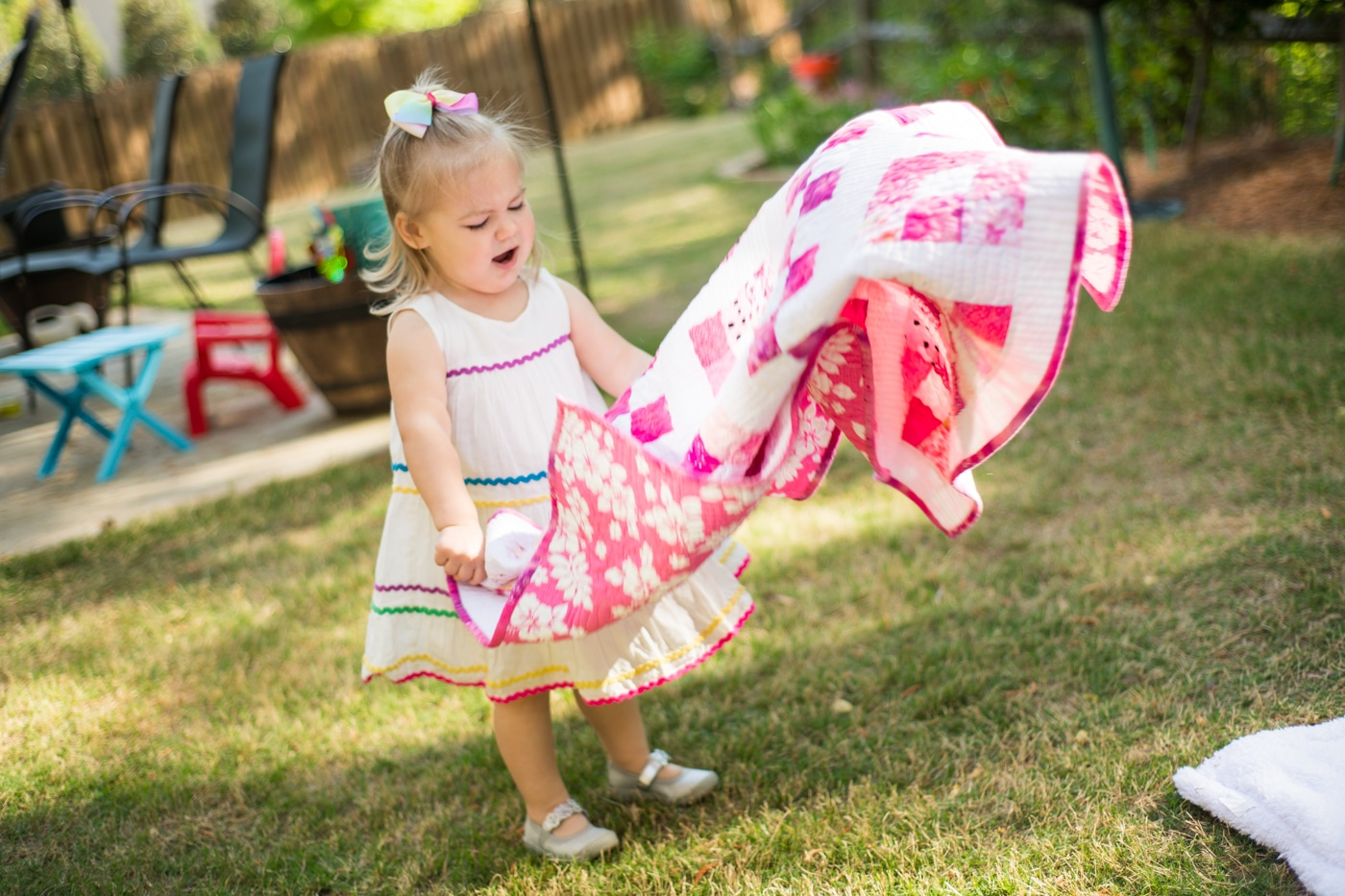 Toddler fluffing a quilt in a backyard in Atlanta Raven Shutley family photographer