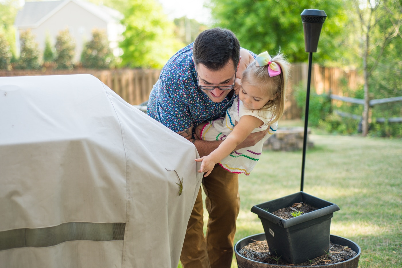Father showing his toddler a lizard in their backyard in Atlanta family portraits Raven Shutley