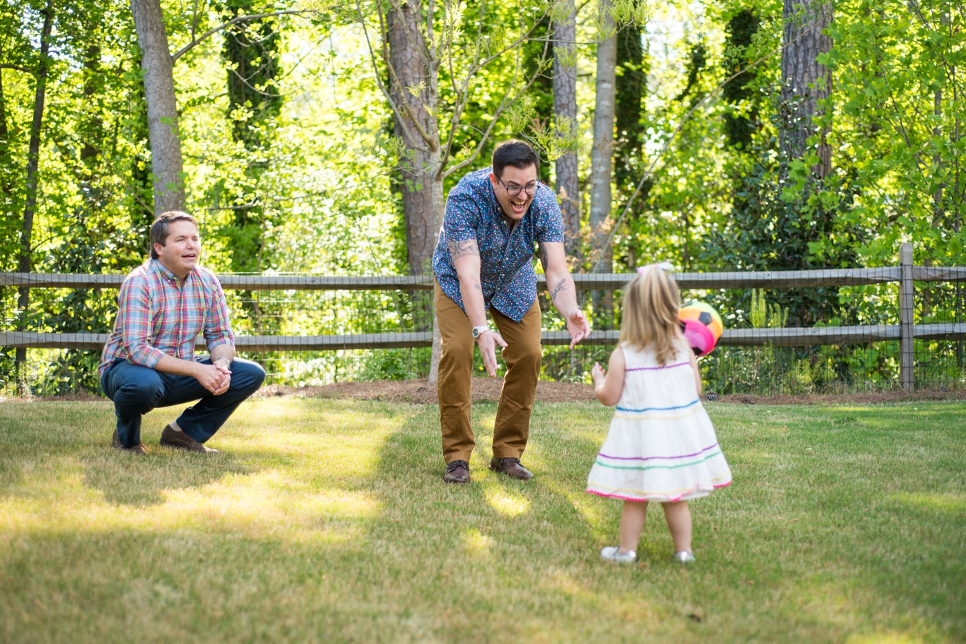 Dads playing with their toddler in their backyard in Atlanta Raven Shutley family photographer