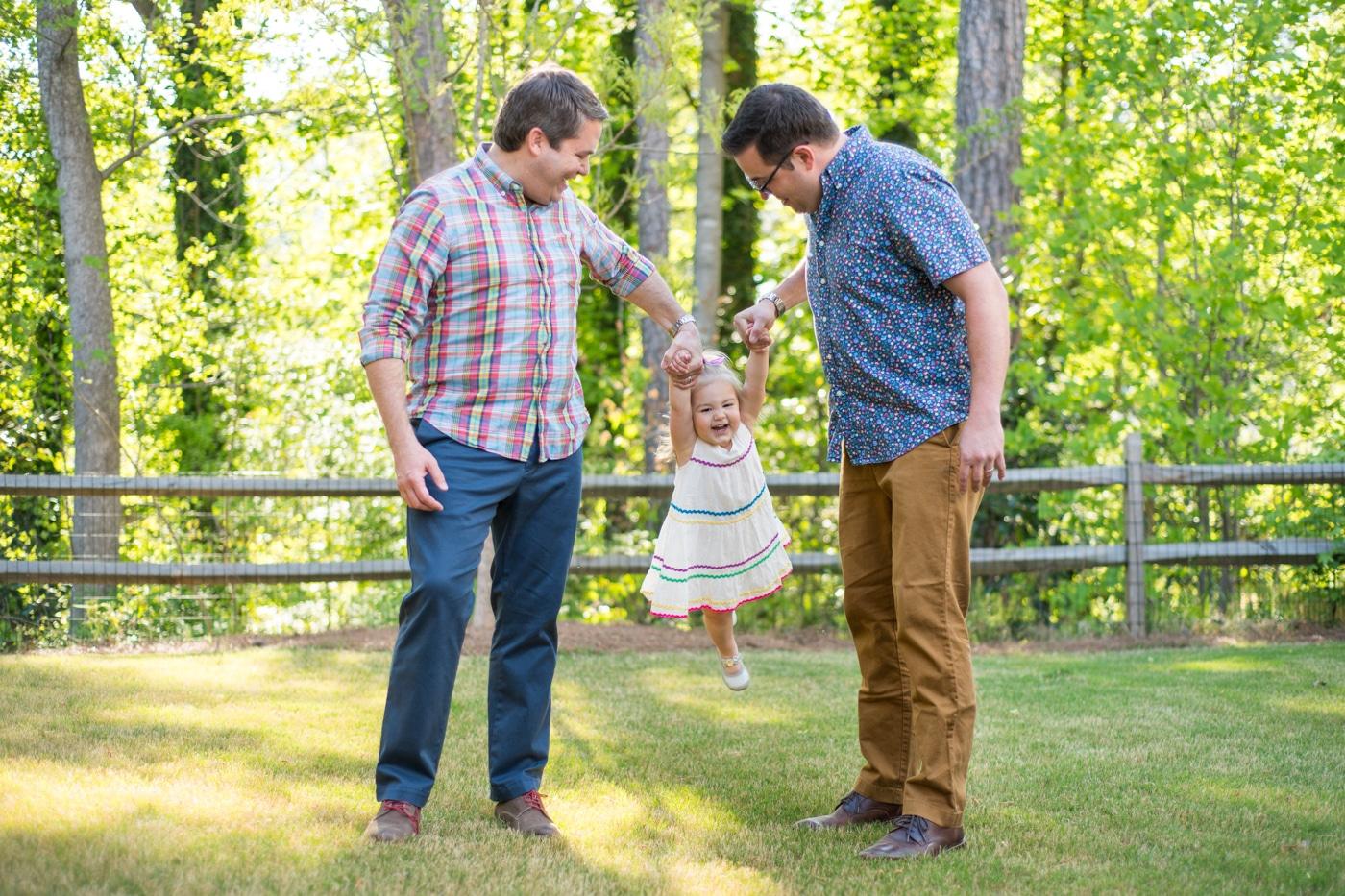 Dads swinging their toddler on a sunny day in Atlanta GA Raven Shutley Studios family photos