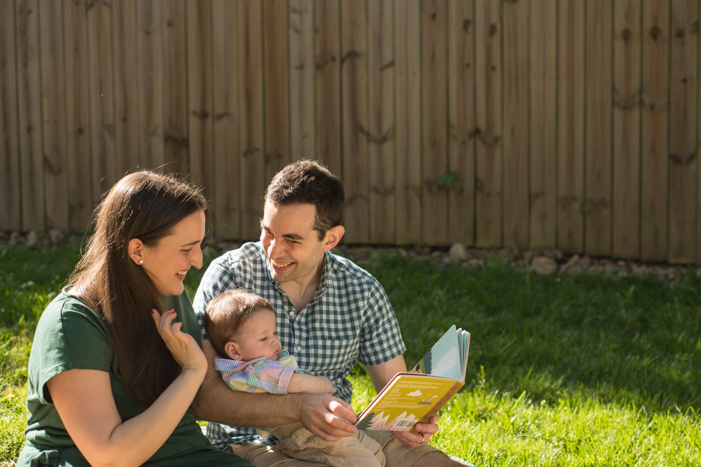 Married couple holding their baby and laughing over a kid's book in Atlanta backyard Raven Shutley