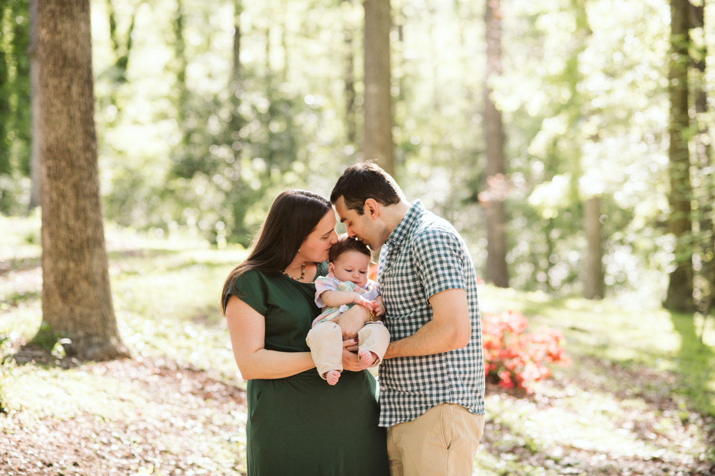 Young parents kissing their baby son together in a park in ATL Raven Shutley Family Photos
