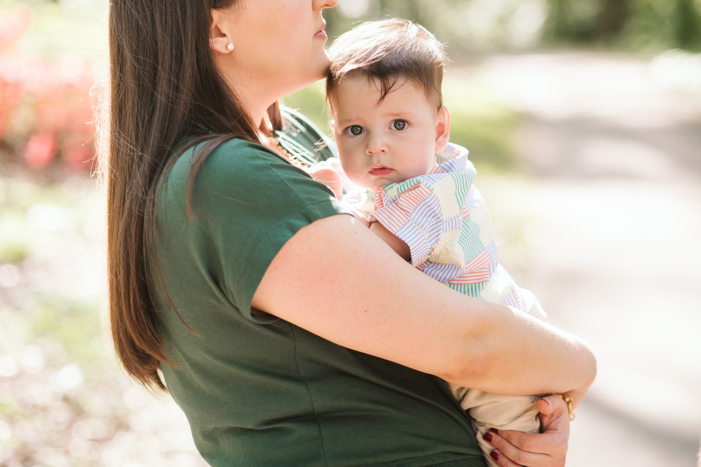 Mother in green holding her baby son at a sunny park in Atlanta Raven Shutley Studios family photos
