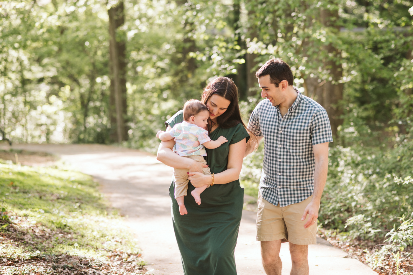 Mother holding her baby and walking with her partner through a park in ATL Raven Shutley Studios
