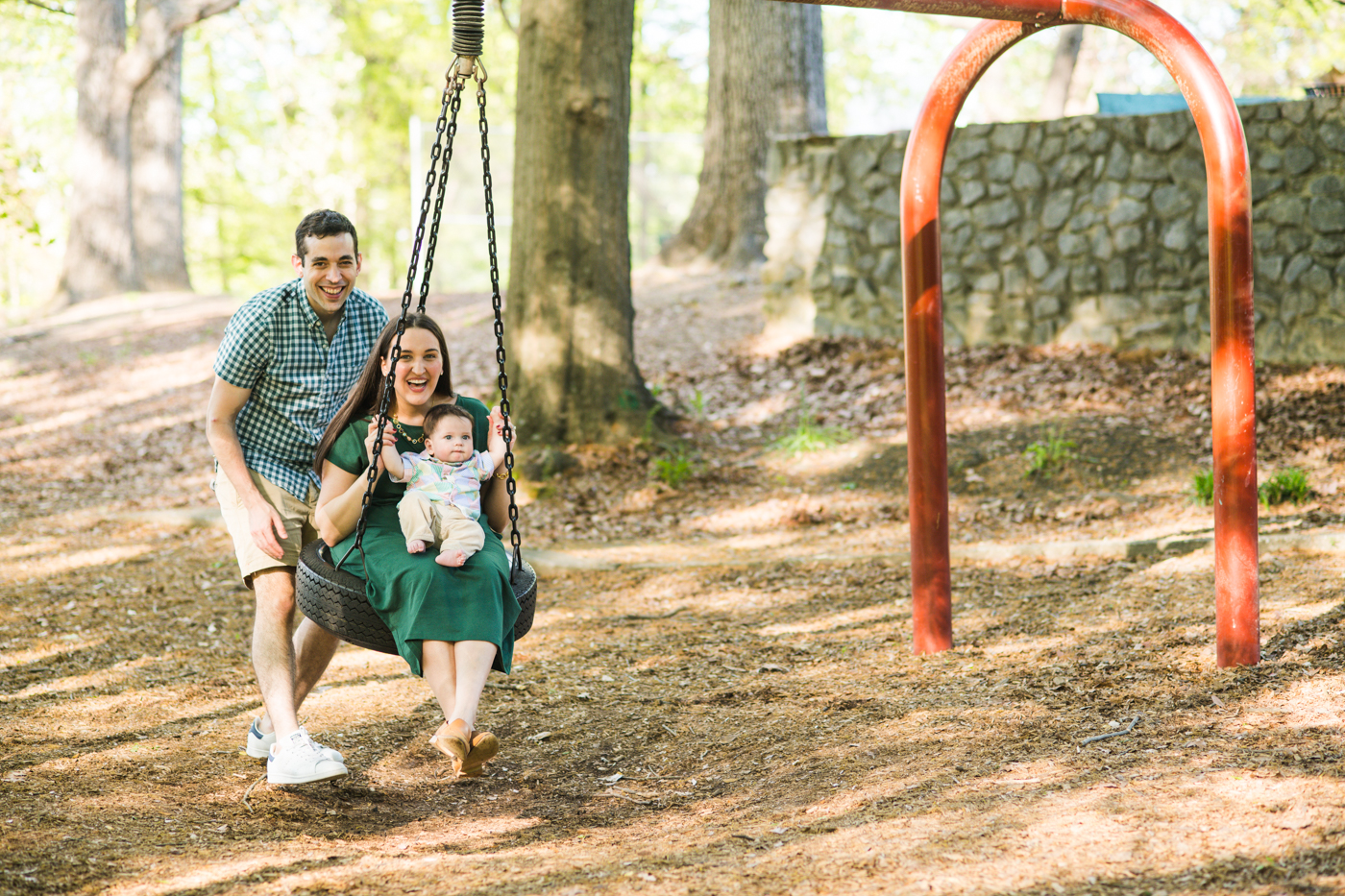 Father pushing mother and baby on a swing in Atlanta GA Raven Shutley lifestyle family photos
