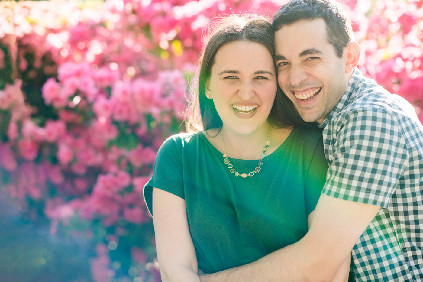 Married couple embracing in the sun by large pink flowers in Atlanta GA Raven Shutley Studios