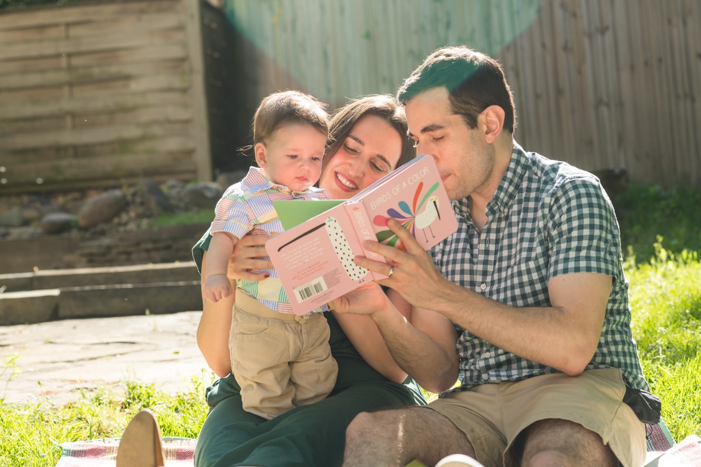 Married couple with their baby reading a book in Atlanta Raven Shutley Studios family portraits