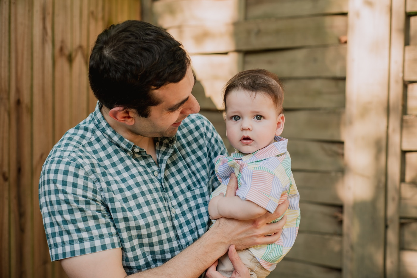 Dad holding his baby son during Lifestyle Family Photos in Atlanta Backyard by Raven Shutley Studios