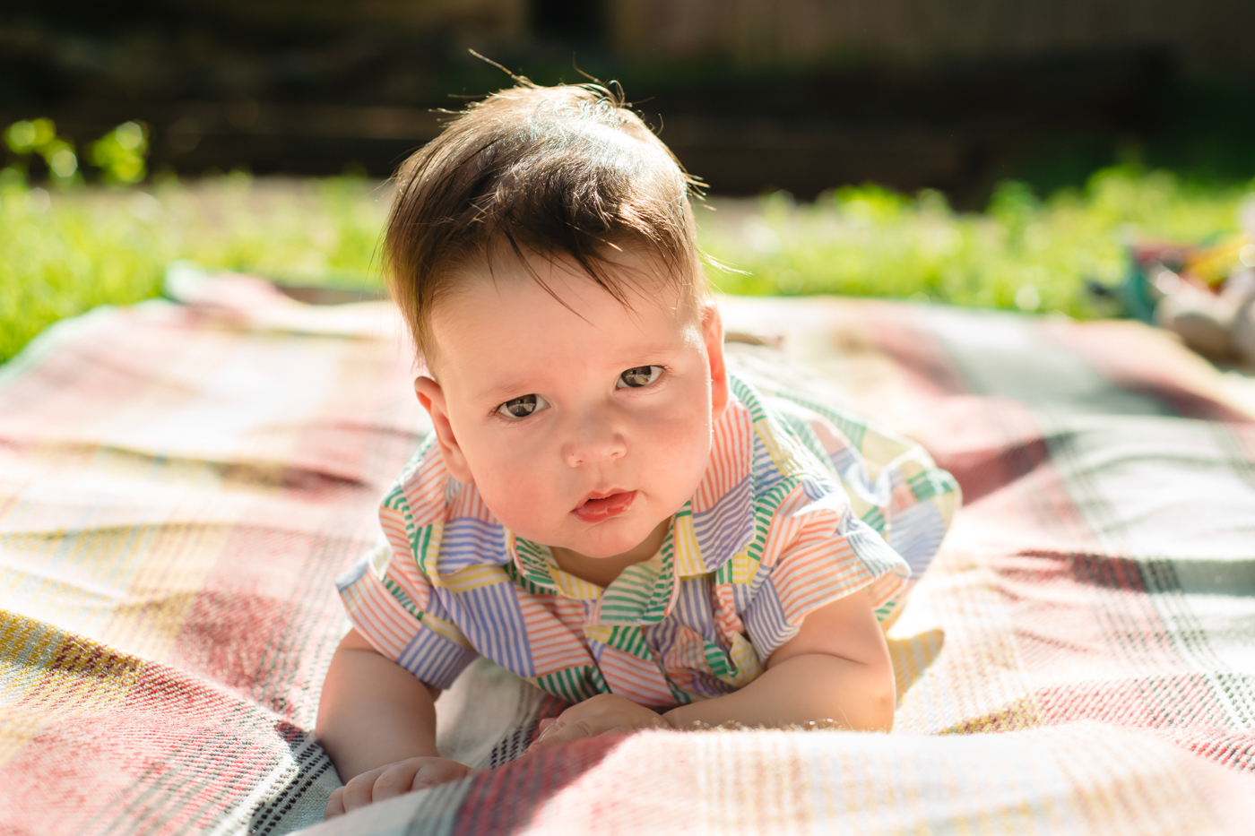 Toddler in a colorful button-up laying on blanket at Atlanta home Raven Shutley Studios