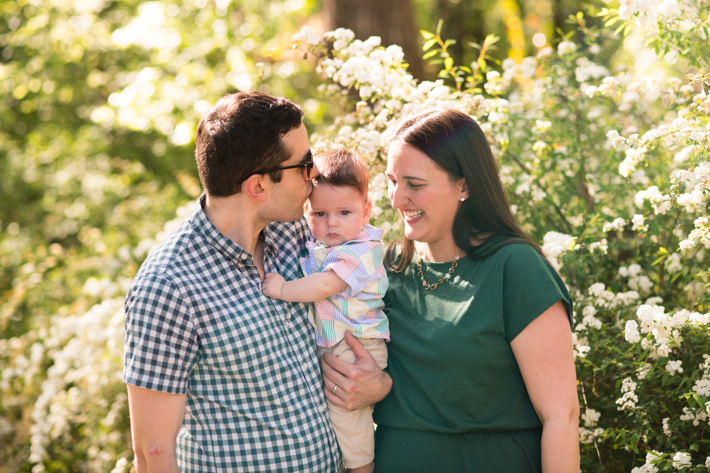 Young family with baby smiling in a garden during ATL family photoshoot by Raven Shutley Studios