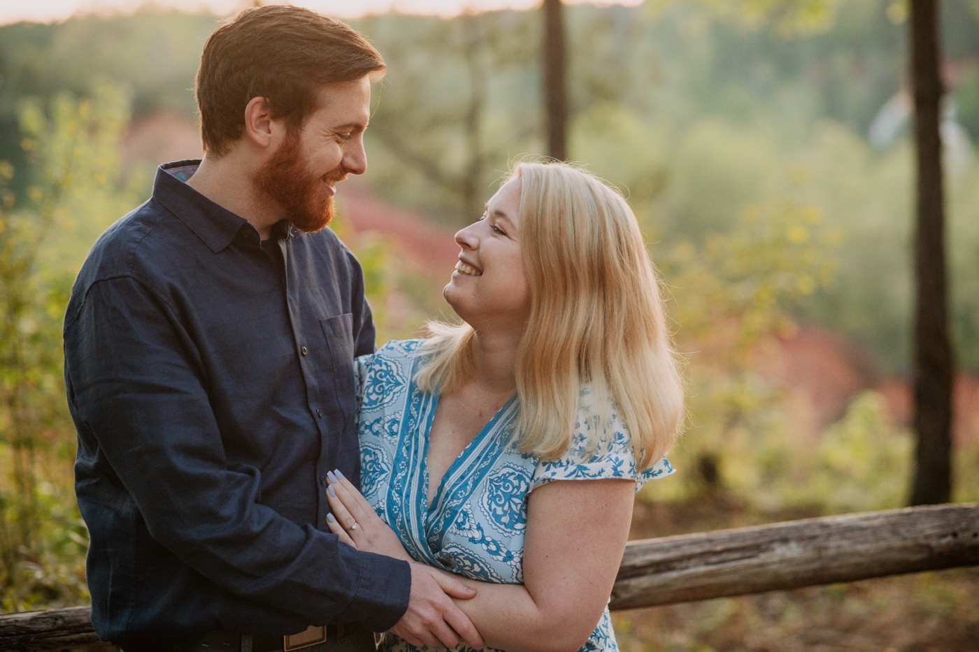 couple smiles together by wooden fence in Providence Canyon