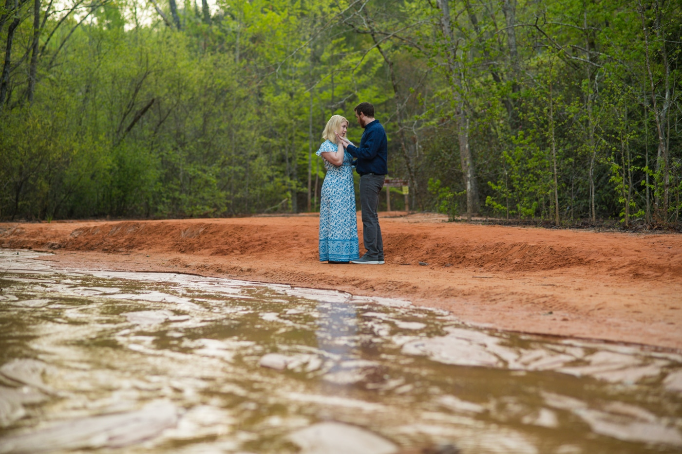 engaged couple dances by river in Georgia state park