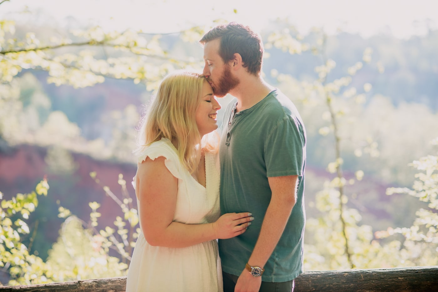 groom kisses bride's forehead during GA engagement photos