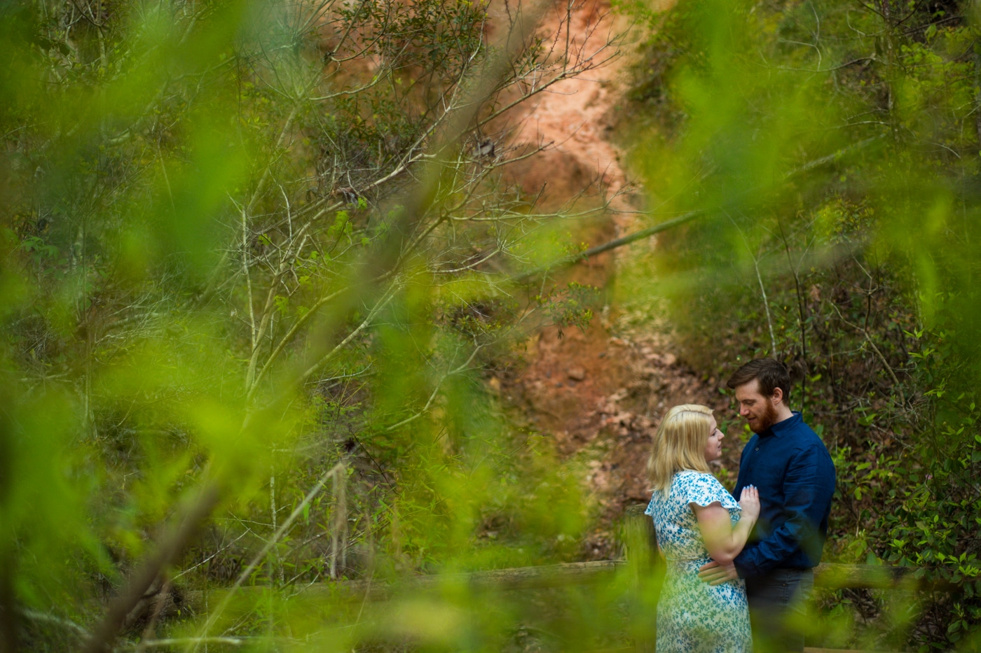couple hugs behind green trees in Providence Canyon