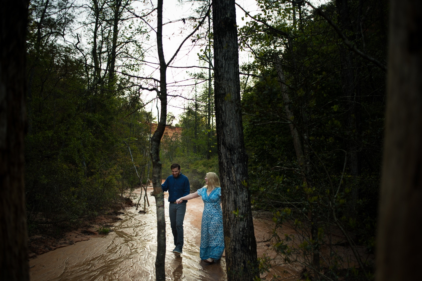 engaged couple holds hands walking through trees in Providence Canyon