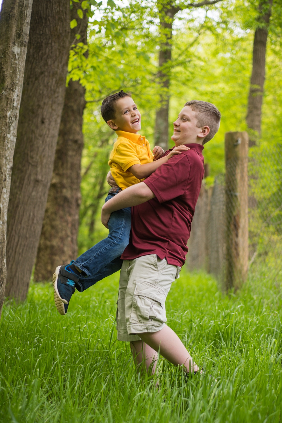 young guy lifts brother up during family photos at Yellow River Wildlife Sanctuary