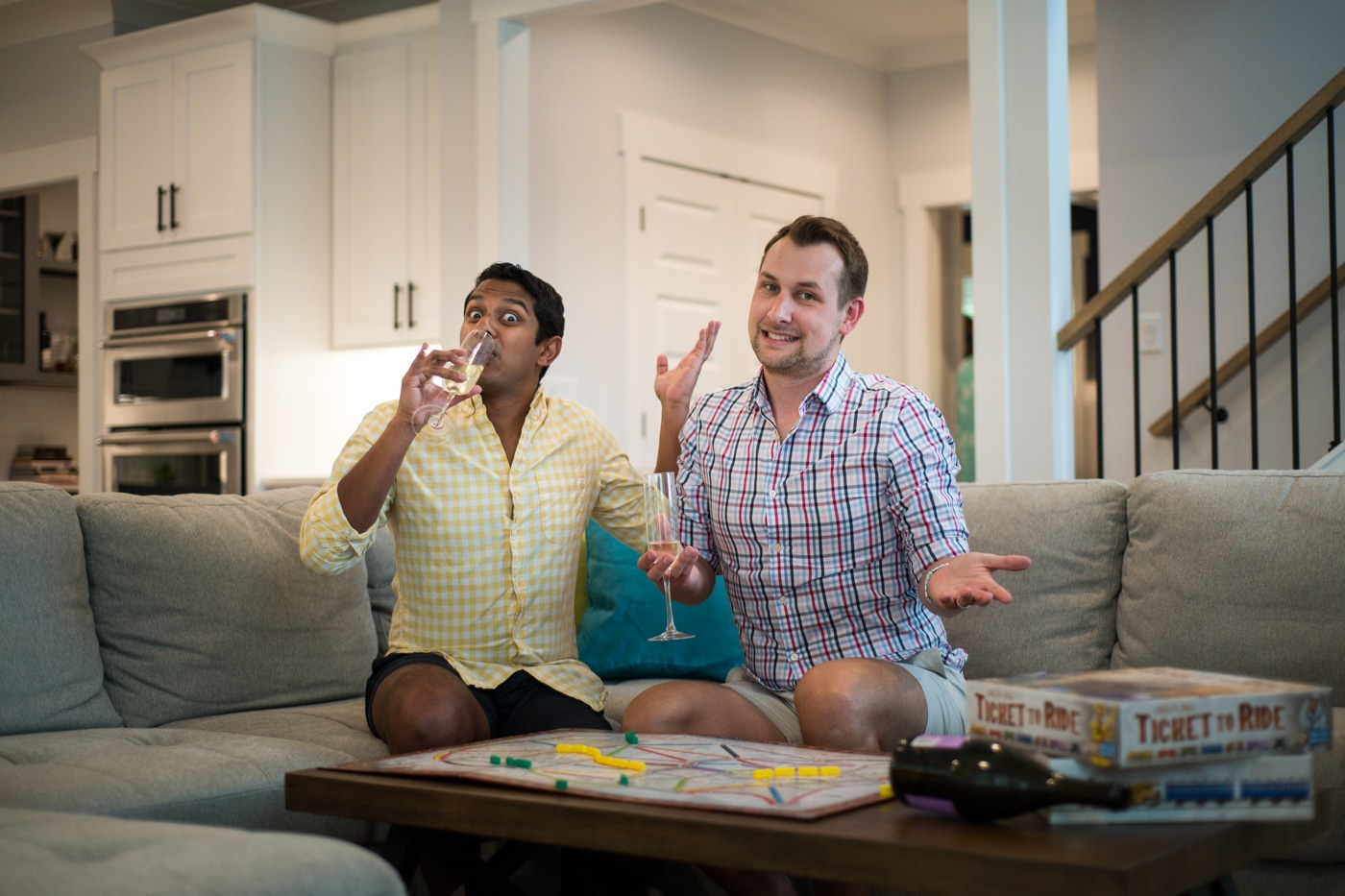 LGBTQ engaged couple sits with Ticket to Ride and laughs in Atlanta GA Raven Shutley Studios