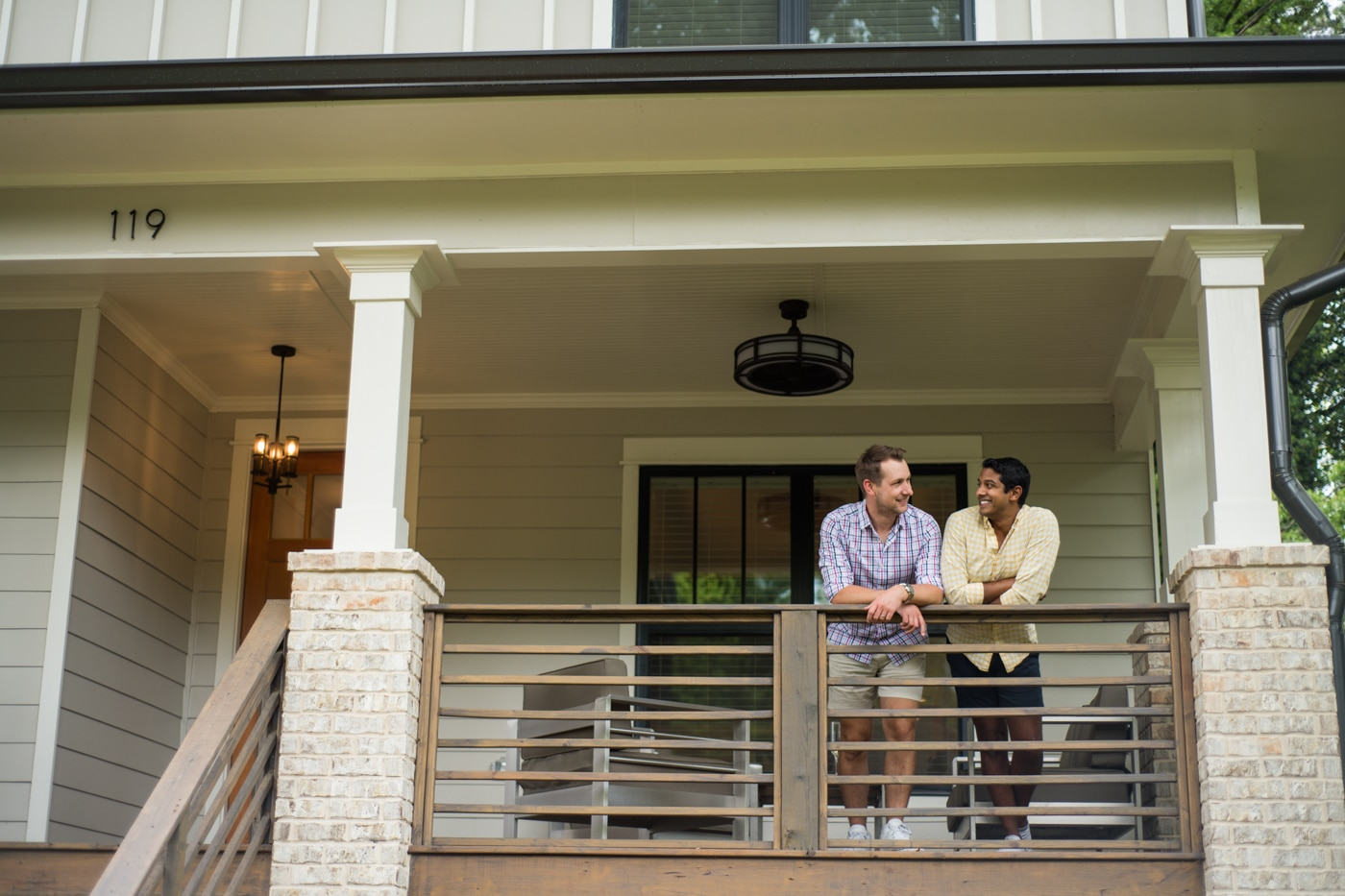 Engaged couple leaning on porch railing at their house in Atlanta GA Raven Shutley Studios