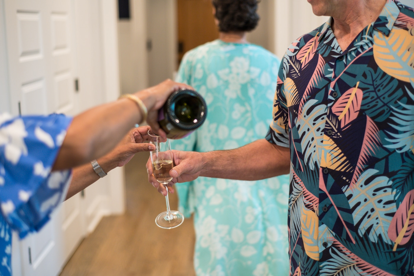 Family of engaged couple pours champagne into a glass in Atlanta GA Raven Shutley Studios