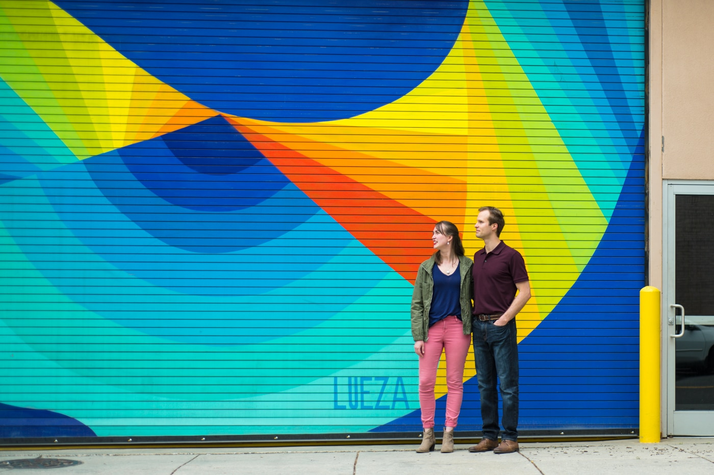 couple poses by rainbow mural in downtown Durham NC