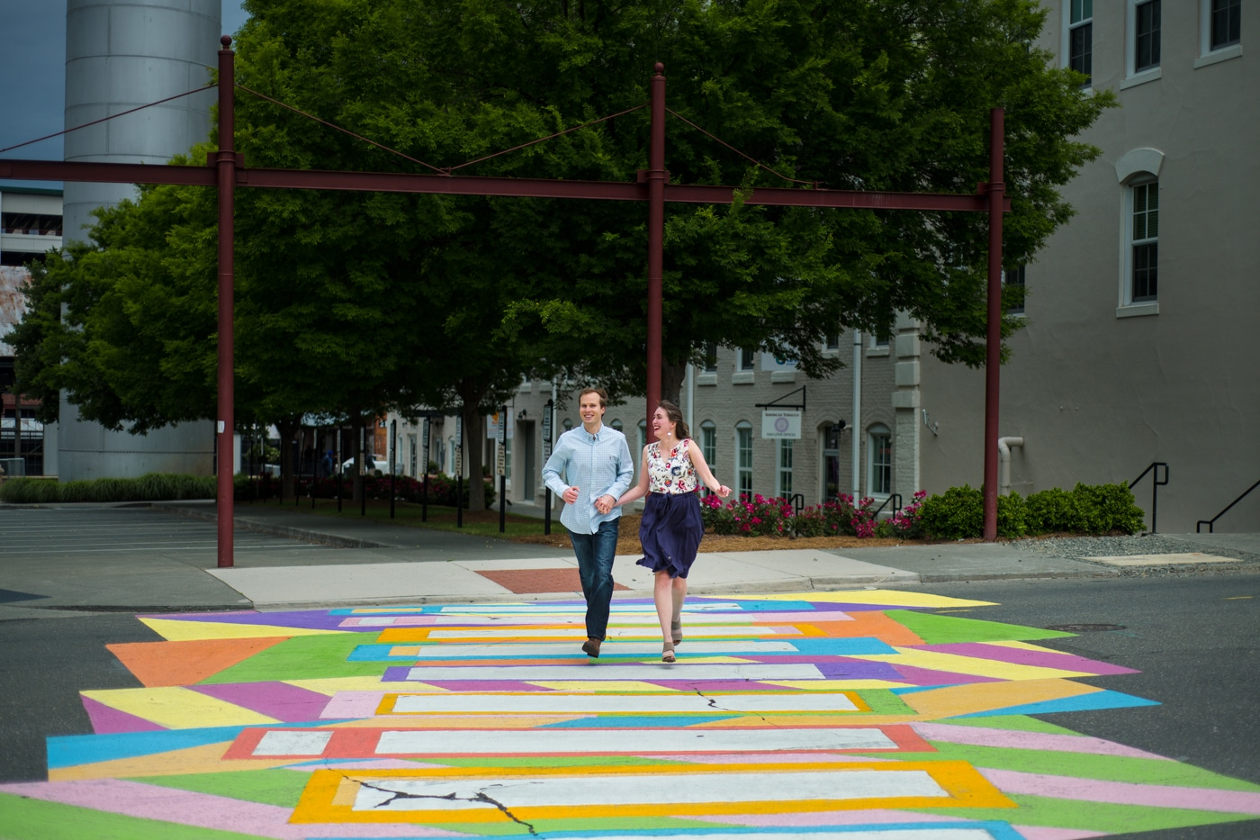 bride and groom walk on colorful crosswalk during Durham engagement session